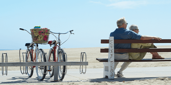 Mature couple at beach with bikes