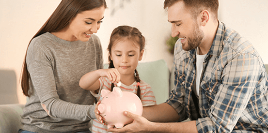 Small young family putting money in a piggy bank